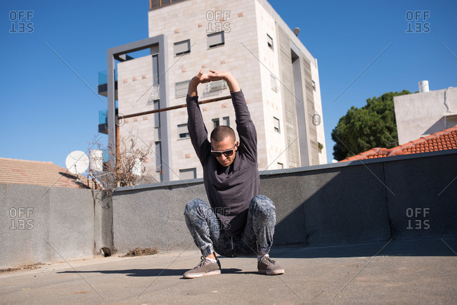 Man stretching his arms on the roof of a building