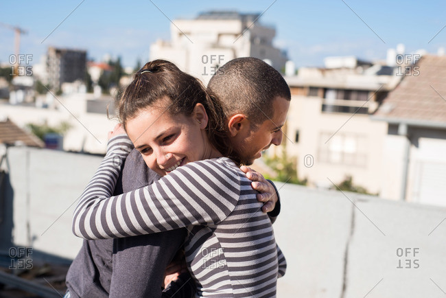 Young man and young woman embracing on the roof of a building