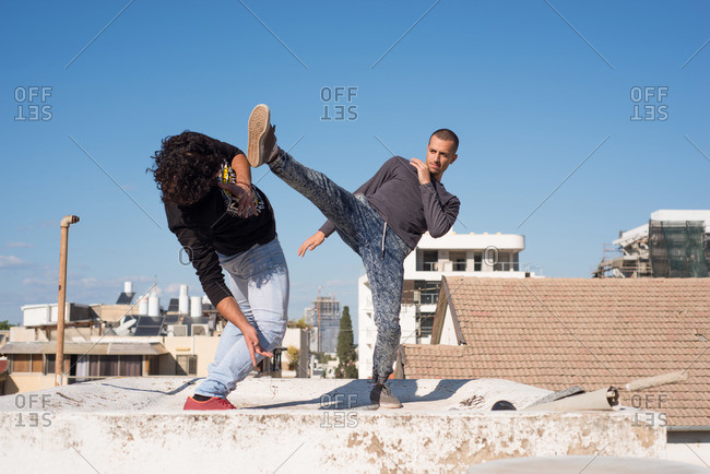 Man performing a martial art on the roof of a building