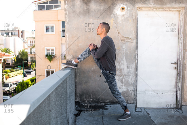 Man stretching his leg against the side of a wall