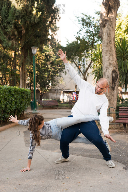 Man and woman stretching on a path in a neighborhood park