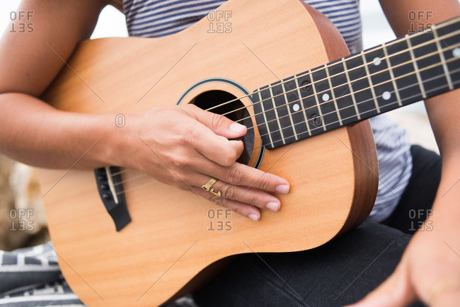 Close-up view of a woman holding a guitar