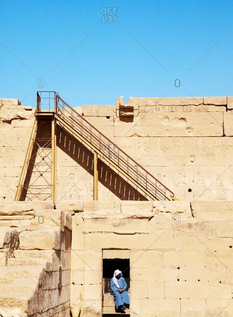 Egypt - January 29, 2013: Man sitting amongst ancient Egyptian ruins