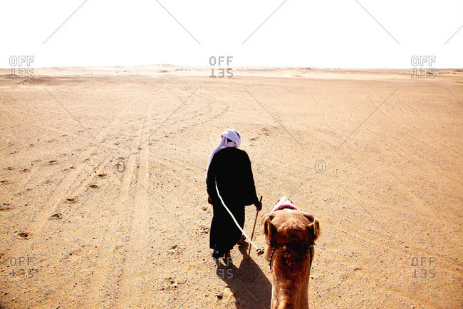 Man leading a camel across desert in Egypt