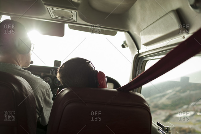 Boy sitting next to pilot during a ride in a small plane