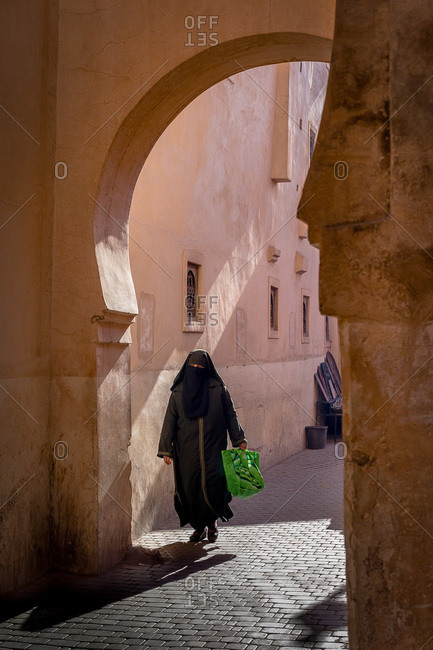 Woman walking on a cobblestone street in Marrakech, Morocco