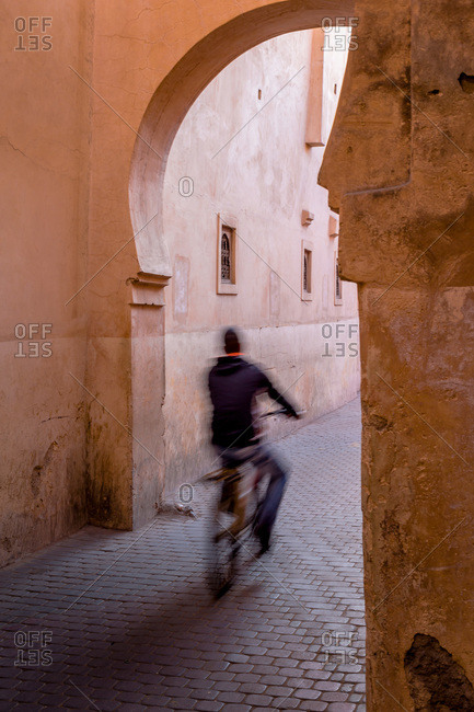 Person cycling on a cobblestone street in Marrakech, Morocco