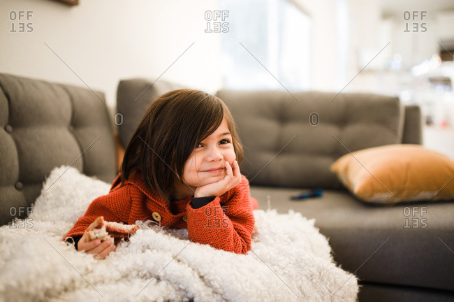 Happy girl lying on couch while eating a sandwich