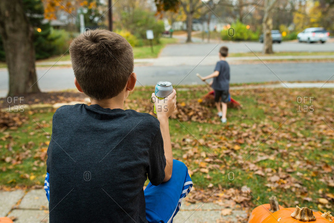 Boy watching younger brother rake leaves