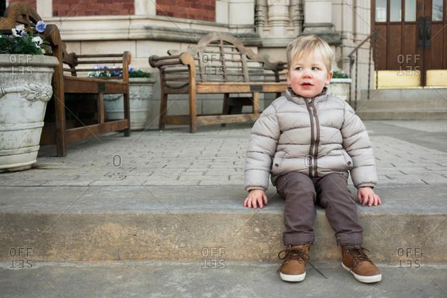 Little boy sitting on a step