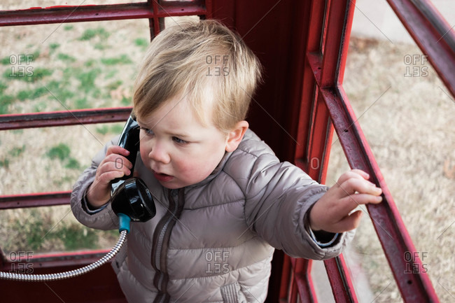 Boy on the phone inside a telephone booth