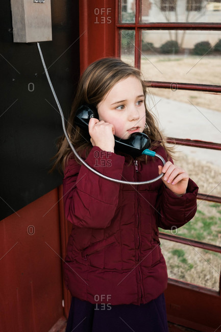 Girl on the phone inside a telephone booth