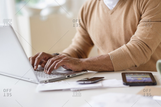 Man working with laptop at table at home
