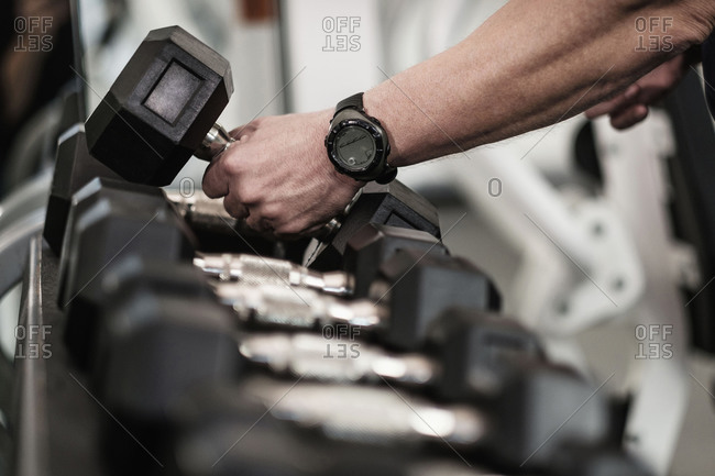 Man picking up dumbbells in health club