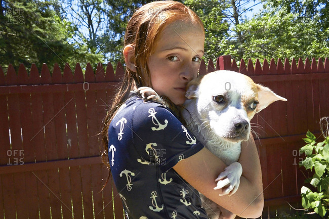 Portrait of teen girl holding dog in backyard