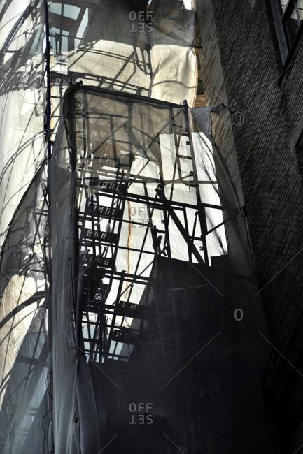 Shadow of a fire escape seen through a large tarp