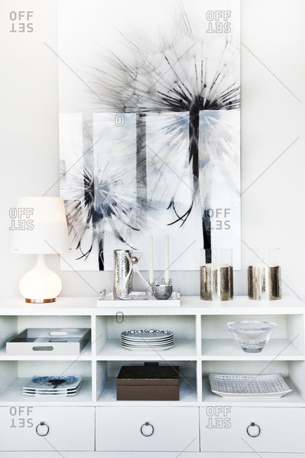 Low white bookcase with accessories and a large flower print