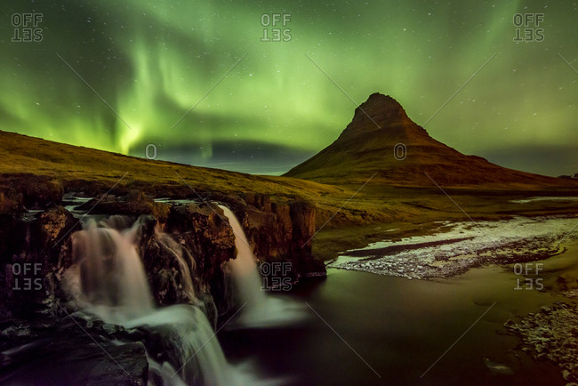 The Aurora exploding in green over a waterfall