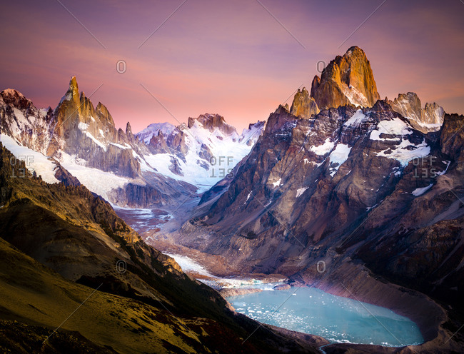 Snow covered mountain peaks and glacier under a pink sky
