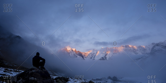 A man looking out over sun lit mountain range