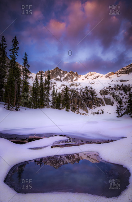 Blue ponds surrounded by snow with mountains in the background under a pink sky