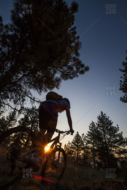 A woman mountain biker silhouetted in the rising sun at Blue Mountain Recreation Area in Missoula, Montana
