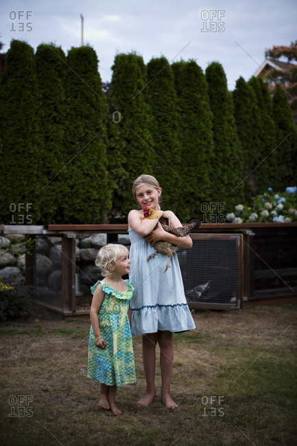 Two sisters stand in front of the family chicken coop in Seattle, WA