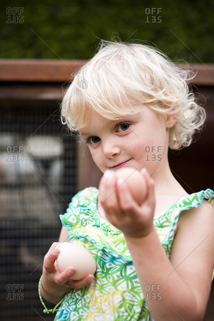 A young girl holds two eggs she gathered from her family's backyard coop