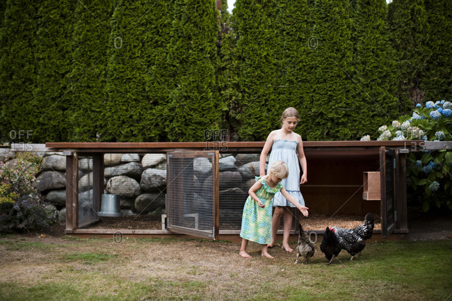Two young girls stand in front of the family chicken coop in Seattle, WA