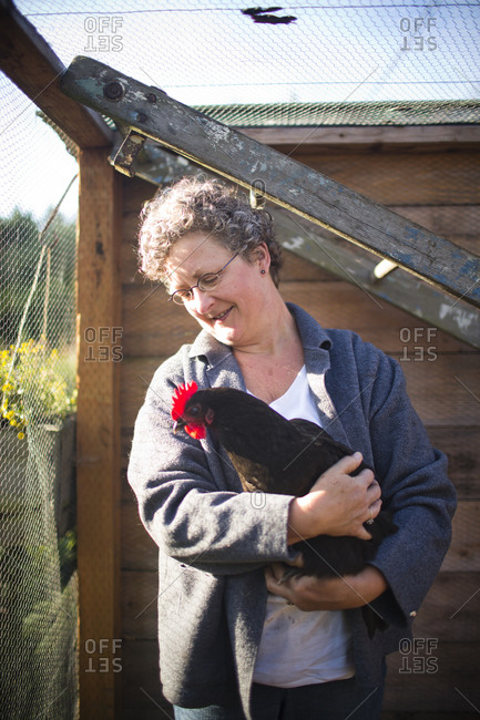 A mature woman holding a chicken in a backyard coop in Austin, Texas