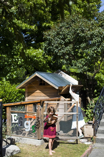 A woman with her daughter tending to a backyard chicken coop