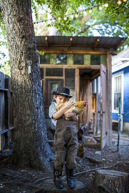 A boy in a cowboy hat hold a chicken