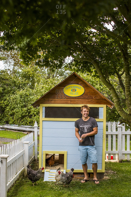 Man standing in front of his backyard chicken coop