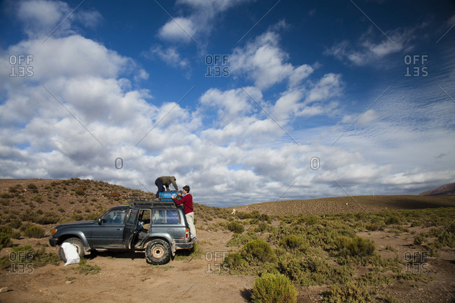 Salar de Uyuni, Bolivia, Bolivia - March 28, 2010: A man unloads gear from the roof of a truck in the Atacama Desert