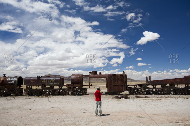 A man takes a photo of a deserted train in the Atacama Desert