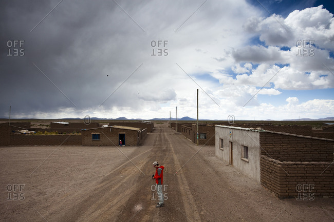 A man walks down a lonely dirt road underneath a blue sky in the middle of the desert