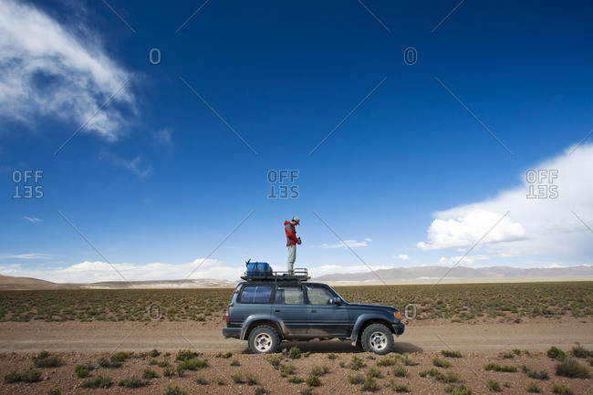 Salar de Uyuni, Bolivia, Bolivia - March 28, 2010: A man stands on the roof of his truck to take a photo