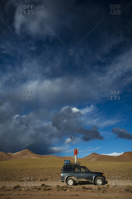 Salar de Uyuni, Bolivia, Bolivia - March 28, 2010: A man stands on the roof of his truck to take a photo of the dramatic clouds approaching