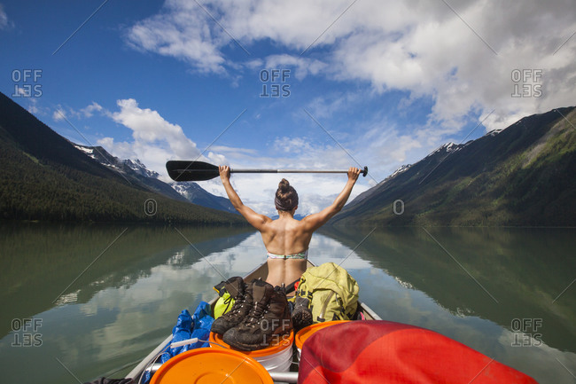 A young holds her paddle above her head while canoeing across Lanezi Lake in Bowron Lake Provincial Park