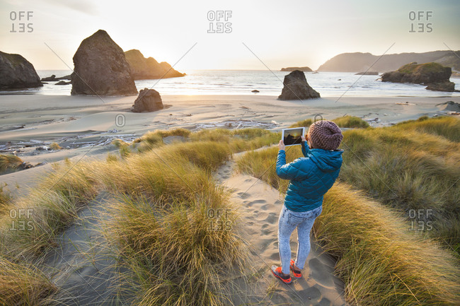 Woman taking a picture with a tablet at dusk on Gold Beach