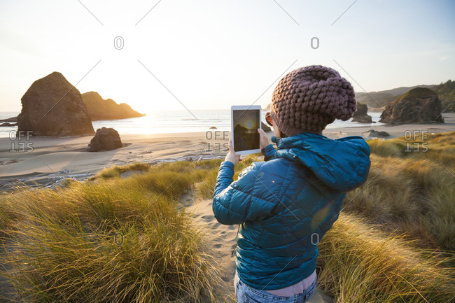 Woman taking a picture with a tablet of a sunset over Gold Beach