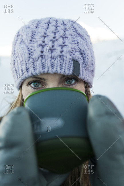 A young active woman enjoys a hot drink during a winter camping trip