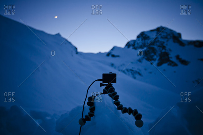 An HD camera sits on a tripod supported by a block of snow, set up to capture a time-lapse of the night sky