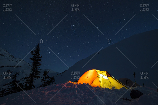 A headlamp is used to light up a tent below a starry night sky in British Columbia, Canada