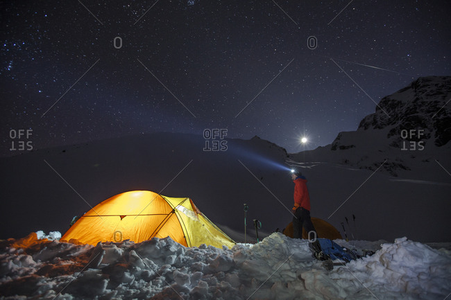 Climber standing beside his lit up tent under a starry night sky