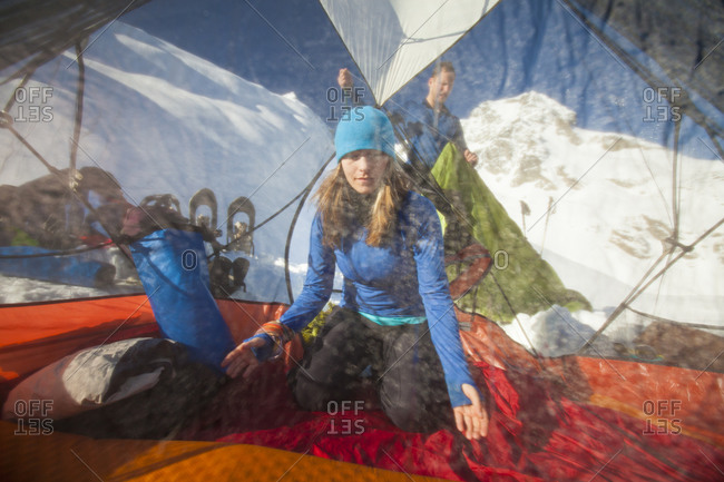 An active woman works to re-pack her sleeping bag and mattress after camping overnight in the Coast Mountain Range