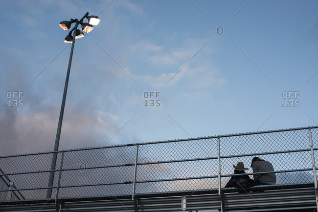A young cowboy in a cowboy hat and his mom in the stands watching a rodeo