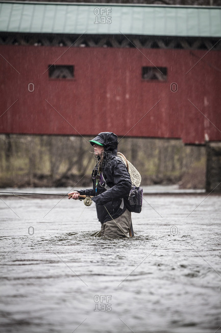A female angler fishes underneath a red covered bridge in spring rain