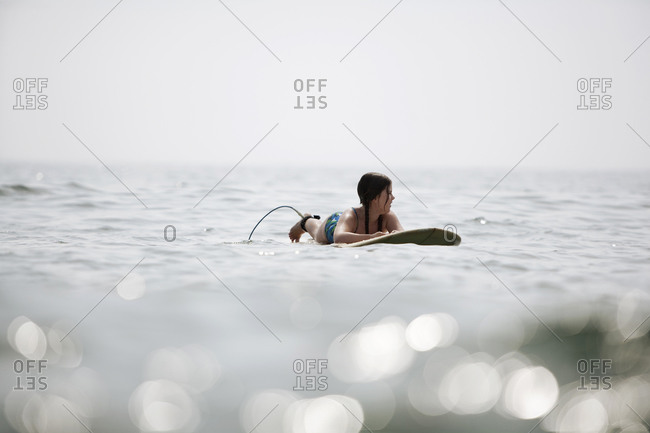 A young girl waits for a wave while drifting on her surfboard