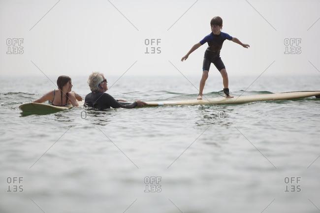 A grandfather teaches grandchildren how to balance on a surfboard